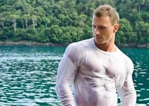 Handsome young bodybuilder by the sea with wet shirt on